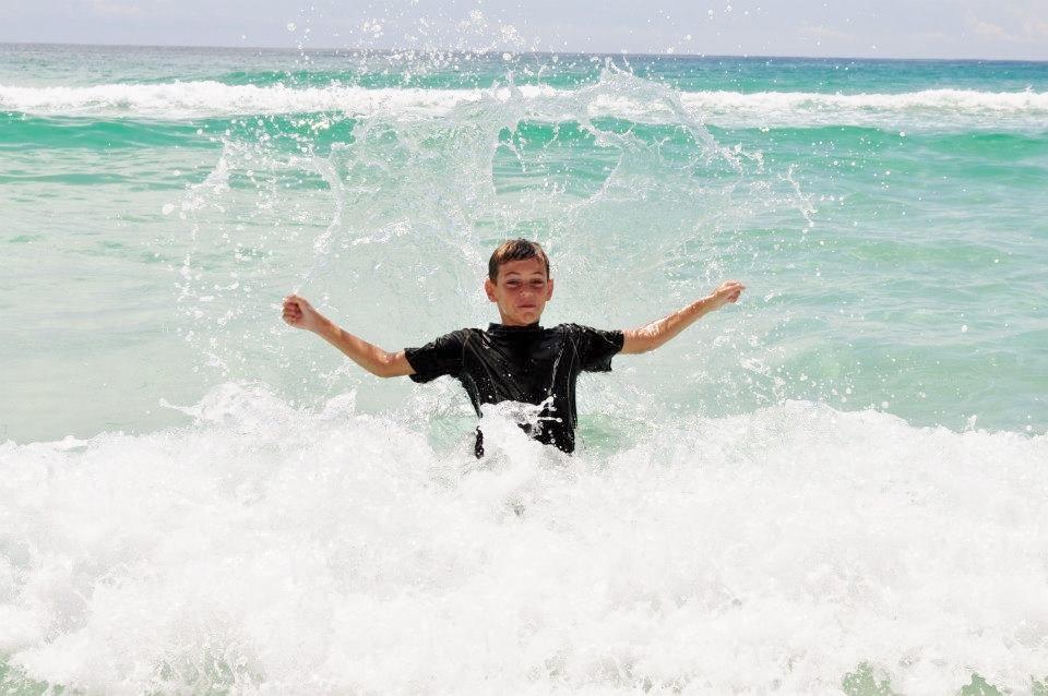 Boy in waves in Destin at Sandnsol